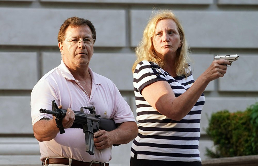 """Ken and Karen of St. Louis defending their home after a mob smashed one of their statues. They were later charged with felony weapons count, for their """"eyes were full of fire."""""""